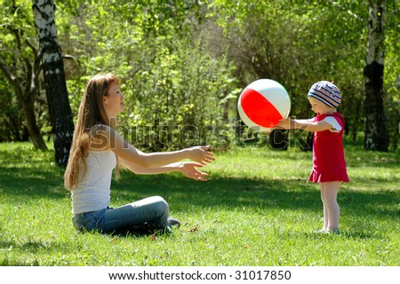 Mother and child play with ball - stock photo