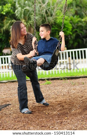 mother and child playing at park on swing - stock photo