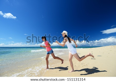 Mother and child playing at the beach - stock photo