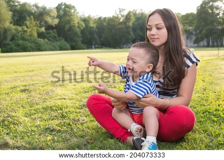 mother and child playing at the grass. naughty boy crying and and point by his finger. copy space left.