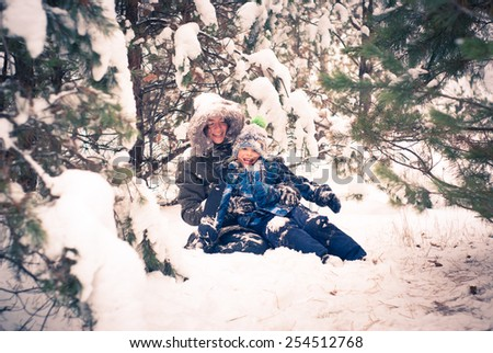 Mother and child playing in snowy winter outdoor - stock photo