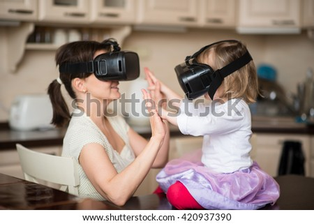 Mother and child playing together with virtual reality headsets indoors at kitchen
