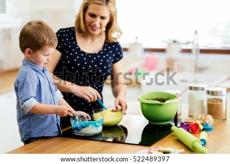 Mother and child preparing cookies in kitchen