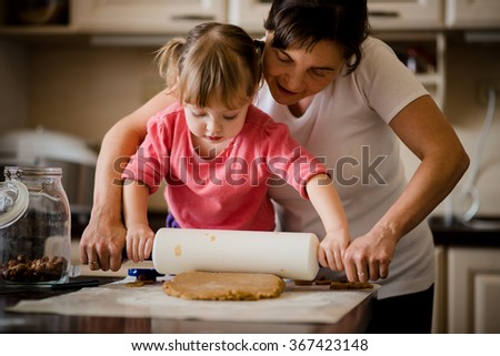 Mother and child preparing dough with rolling pin in kitchen at home - stock photo