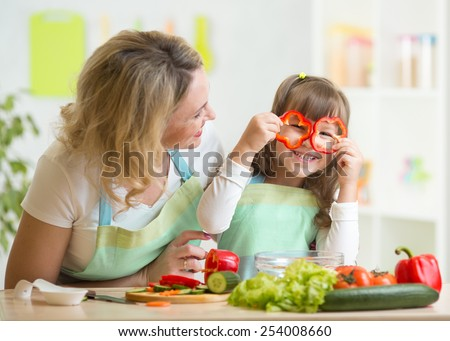 mother and child preparing healthy food and having fun - stock photo