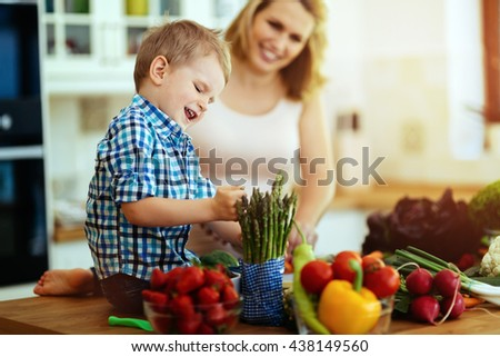 Mother and child preparing lunch in kitchen - stock photo
