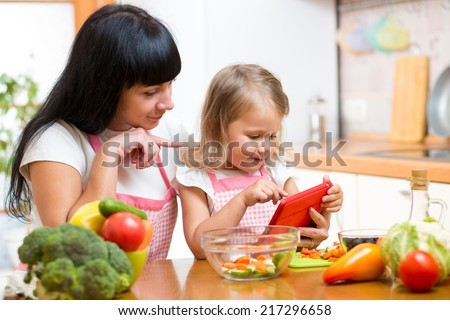 Mother and child preparing vegetables together at kitchen and looking at tablet for recipe - stock photo