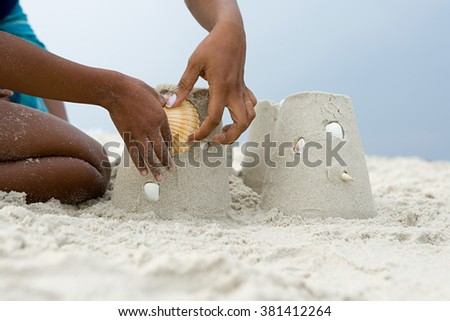 Mother and child putting a shell on a sandcastle - stock photo