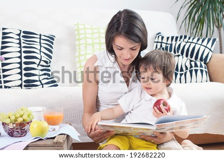Mother and child, reading a book and eating fruits