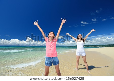 Mother and child relax at the beach - stock photo