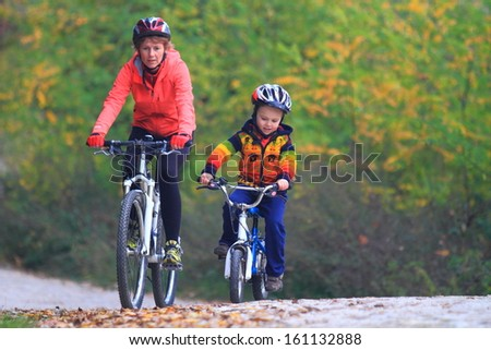 Mother and child riding bikes together during autumn