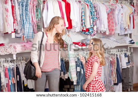 mother and child shopping choosing dress in clothes shop - stock photo