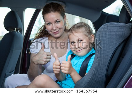 Mother and child showing thumb up gesture in car safety seat - stock photo