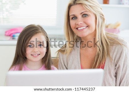 Mother and child sitting and smiling at the kitchen with laptop