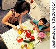 Mother and child son cut vegetables for a meal food in the kitchen - stock photo