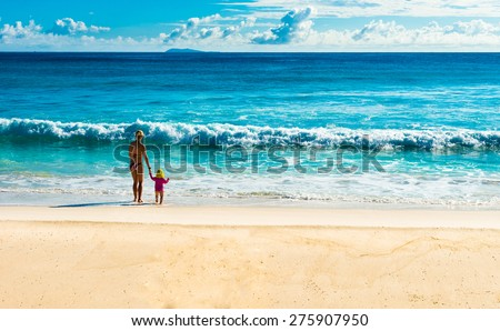 mother and child standing on tropical beach