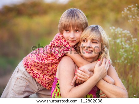 mother and child together in a meadow - stock photo