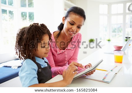 Mother And Child Using Digital Tablet For Homework - stock photo