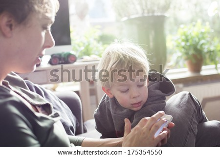 Mother and child using smartphone - stock photo