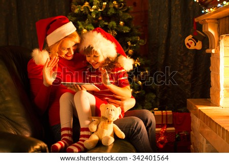 Mother and child using tablet pc to communication with dad on Christmas evening - stock photo