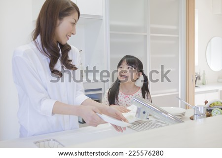 Mother and child washing dishes - stock photo