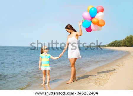 Mother and child with colorful balloons walking on beach near sea - stock photo