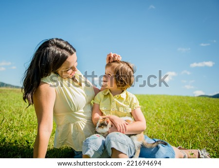 Mother and child with kitten having together great time outdoor in nature