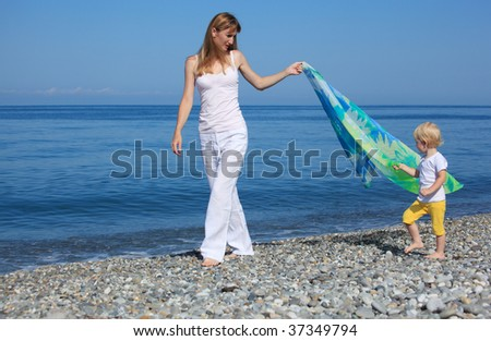 Mother and child with shawl walk on edge of sea - stock photo