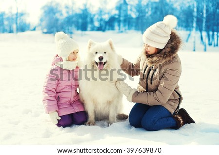 Mother and child with white Samoyed dog together on snow in winter day - stock photo