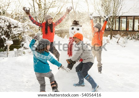 Mother And Children Building Snowman In Garden - stock photo