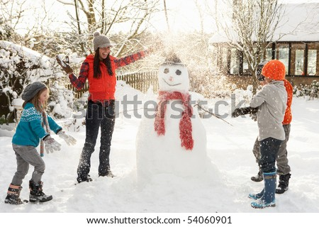 Mother And Children Building Snowman In Garden - stock photo