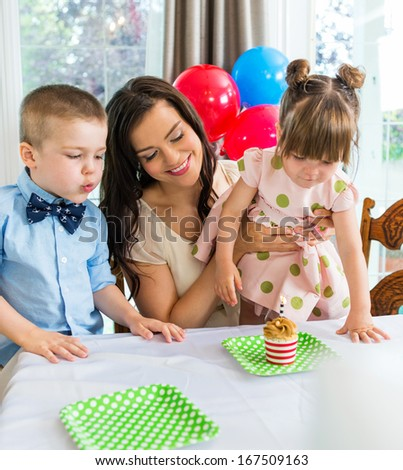 Mother and children celebrating birthday with cupcake on table
