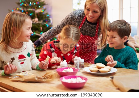 Mother And Children Decorating Christmas Cookies Together - stock photo