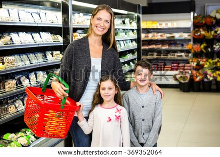 Mother and children doing grocery shopping at the supermarket - stock photo