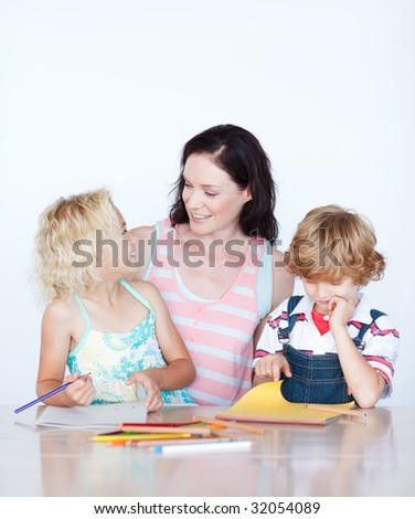 Mother and children drawing together at home - stock photo