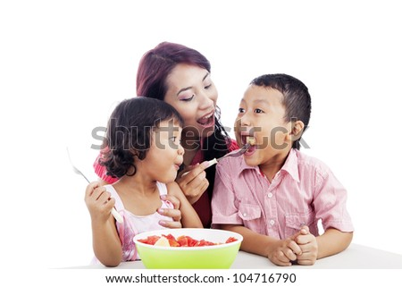 Mother and children eating healthy snack - fruit salad . Shot in studio isolated on white