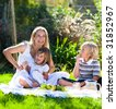 Mother and children having a picnic in a park - stock photo
