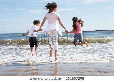 Mother And Children Having Fun On Beach Holiday - stock photo