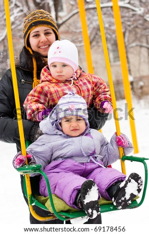 Mother and children in playground outdoor in winter - stock photo