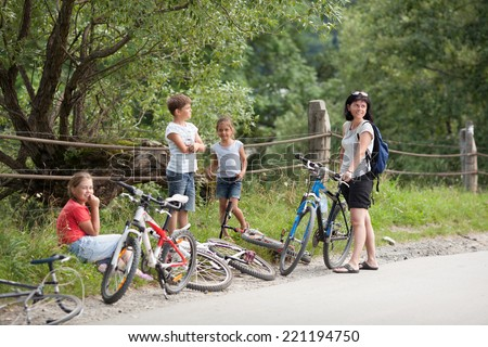 Mother and children in the nature on bicycles - stock photo