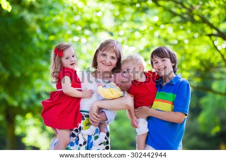 Mother and children play in a park. Woman with newborn baby, little girl, toddler and teenager boy. Siblings with big age difference. Kids with large age gap. Young grandmother with grandchildren. - stock photo