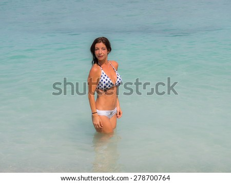 Mother and children playing in a pool in the Caribbean island of Curacao - stock photo