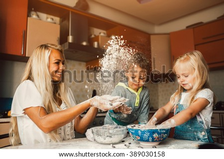 mother and children playing on kitchen with flour - stock photo