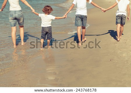 Mother and  children playing on the beach. Concept of friendly family.