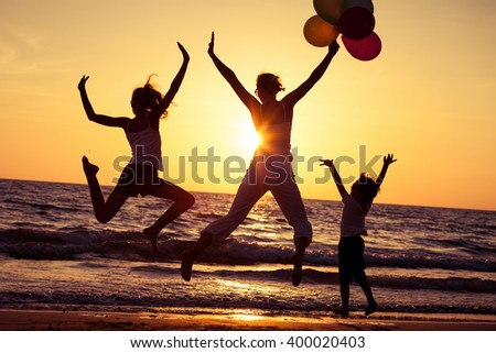 Mother and children playing with balloons on the beach at the sunset time. Concept of friendly family.