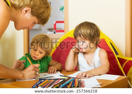Mother and children playing with pencils at home