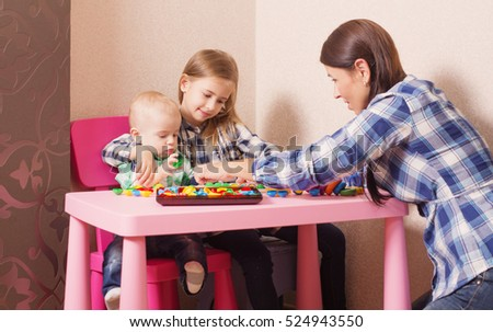 mother and children playing with toys indoor
