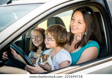 Mother and children pretend driving car sitting all on front seats - stock photo