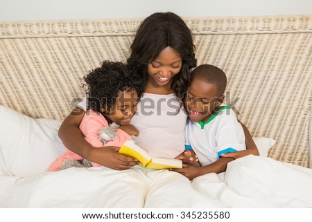 Mother and children reading book together in bed - stock photo