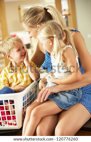 Mother And Children Sorting Laundry Sitting On Kitchen Counter